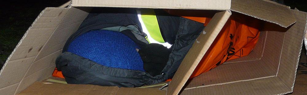 people sleeping in a cardboard box
